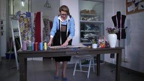 Seamstress που εργάζεται με τα σχέδια στο ράψιμο του ατελιέ απόθεμα βίντεο