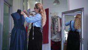 Seamstress που καρφώνει το neckline φορεμάτων στο μανεκέν φιλμ μικρού μήκους