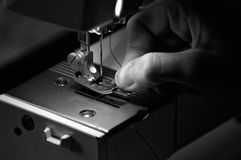Seamstress που περνά κλωστή σε μια ράβοντας μηχανή Στοκ εικόνες με δικαίωμα ελεύθερης χρήσης