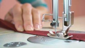 Seamstress ράβει σε μια βιομηχανική ράβοντας μηχανή κλείστε επάνω απόθεμα βίντεο