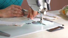 Seamstress ράβει σε μια βιομηχανική ράβοντας μηχανή κλείστε επάνω φιλμ μικρού μήκους