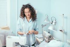 Seamstress της Νίκαιας που φορά τα γυαλιά που κόβουν το ύφασμα για το φόρεμα στο στούντιο σχεδίου Στοκ φωτογραφία με δικαίωμα ελεύθερης χρήσης