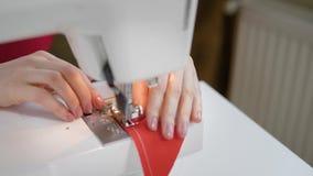 Seamstress κάνει τη βελονιά σε ένα μικρό κόκκινο κομμάτι του υφάσματος από τη ράβοντας μηχανή, που ενώνει δύο τριγωνικά αποκόμματ φιλμ μικρού μήκους
