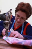 Seamstress. Close-up of a seamstress working with an old sewing machine Royalty Free Stock Image
