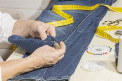 A seamstress. Basting the bottom of the pants Royalty Free Stock Photo