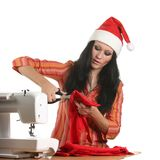 Seamstress in a christmas hat cut cloth Stock Image