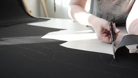 Seamstress cuts out scissor pattern leather for car interior. stock video