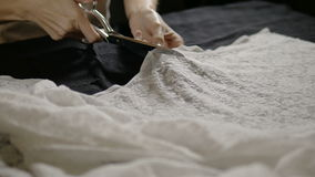 Seamstress cutting clothing fabric with a scissor stock video footage