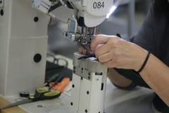 Seamstress hands. Hand of seamstress using sewing machine royalty free stock photo