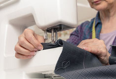 Seamstress hands working on a sewing machine Royalty Free Stock Image