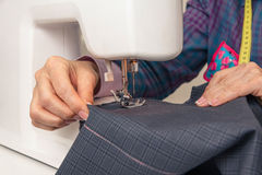 Seamstress hands working on a sewing machine Royalty Free Stock Photo