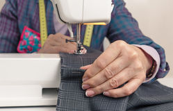Seamstress hands working on a sewing machine Stock Images