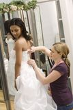 Seamstress helping bride. royalty free stock images