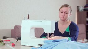 A seamstress at home at the table working with a white sewing machine. She creates new clothes, slow-mo