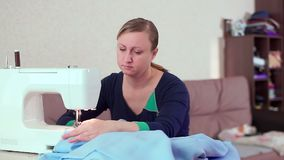 A seamstress at home at the tale working with a white sewing machine. She creates new clothes