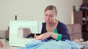A seamstress at home at the tale working with a white sewing machine. She creates new clothes, slow-mo