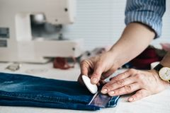 Seamstress marking hem on a pair of jeans in tailor shop. Close up view royalty free stock photography