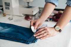 Seamstress marking hem on a pair of jeans. In tailor shop royalty free stock photography