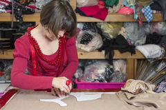 Seamstress Measuring and Cutting Cloth on Cutting Table. A seamstress in red blouse and necklaces measuring and cutting white cloth on cutting table Royalty Free Stock Photo