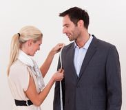 Seamstress measuring a man for a suit Royalty Free Stock Images