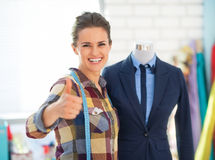 Seamstress near mannequin showing thumbs up Stock Photos
