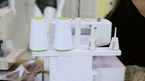 Seamstress opens box with thread and begins to threading overlock. stock video footage