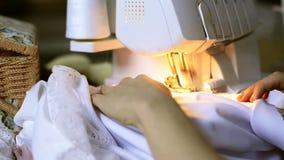Seamstress ράβει το ύφασμα σατέν στο overlock μέσα στο ατελιέ απόθεμα βίντεο