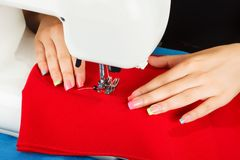 Seamstress sew fabric on the sewing machine. Stock Photo