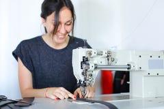 Seamstress sewing belt using sewing machine. Stock Photo