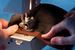 Seamstress Sewing On Velcro Hook-And-Loop Fastener. The hands of a seamstress sewing on a Velcro hook-and-loop fastener stock image