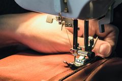 Seamstress sews clothes made of red cloth on a sewing machine. Work by the light of the built-in hardware lamp. Steel needle with looper and presser foot close Royalty Free Stock Photo