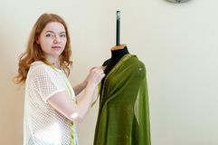 Seamstress standing near mannequin, hanging up cloth and looking at camera royalty free stock images