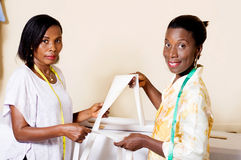 Seamstress and student happy working together in the workshop. Stock Image