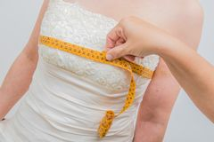 Seamstress take measuring to the bridal dress. A seamstress take measuring to the bridal dress stock photo