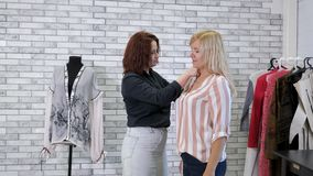 Seamstress takes measurements with tape of woman client in tailoring workshop. Dressmaker works in atelier. Seamstress takes measurements with tape of woman stock video