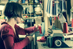 Seamstress Trmming Red Cloth by a Sewing Machine stock photos