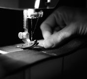 Seamstress Using Sewing Machine. A monochrome shot of a seamstress's hand using a sewing machine to sew on a grosgrain ribbon - square image stock image