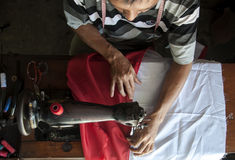 Seamstress. A seamstress was sewing the Indonesia flag Royalty Free Stock Photography