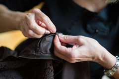 Seamstress. Woman hands sewing a dress Stock Photography