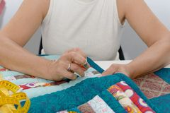 Woman hands sewing for finish a quilt. Royalty Free Stock Photography