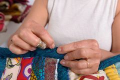 Woman sewing for finish a quilt. Stock Photo