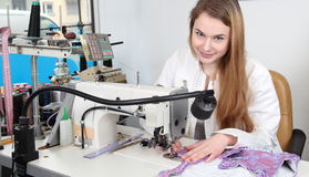 Seamstress woman sewing in a  tailors shop Stock Photo