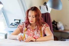 Seamstress woman at work. Young pretty needlewoman at studio sewing fabric Royalty Free Stock Image