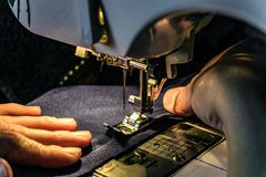 Seamstress work on the sewing machine. Night work by the light of the built-in hardware lamp. Machine sewing needle with looper and presser foot close-up Royalty Free Stock Images