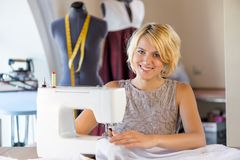 Seamstress at work. Young attractive needlewoman at studio working with sewing machine Royalty Free Stock Photo
