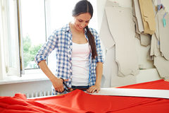 Seamstress working with  pattern and red textile. Smiley seamstress working with  pattern and red textile Royalty Free Stock Image