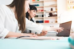Seamstress working at sew studio. Two women dressmaker develop and making new concept clothing with modern laptop. Small sewing business royalty free stock images