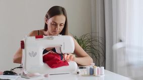 Self-employed seamstress woman working and sewing cloth on sewing machine. stock video
