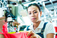 Seamstress i en kinesisk textilfabrik Arkivbilder