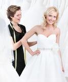 Seamstressen justerar klänningen av bruden arkivbild